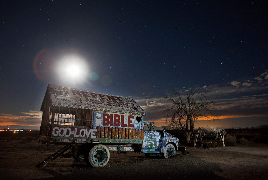 Moon and stars above truck at Salvation Mountain Slab City California
